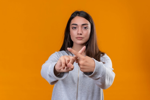 오렌지 배경 위에 서있는 x 제스처를 만드는 회색 hoody에서 젊은 아름 다운 소녀