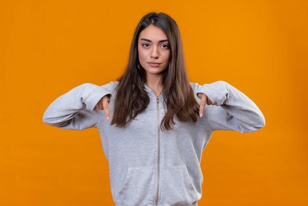 오렌지 배경 위에 불쾌한 서있는 아래로 가리키는 회색 hoody에서 젊은 아름 다운 소녀