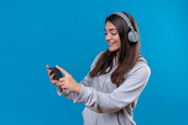 電話を押しながら青い背景の上に立っている電話を見てヘッドフォンで灰色のフーディの美しい少女
