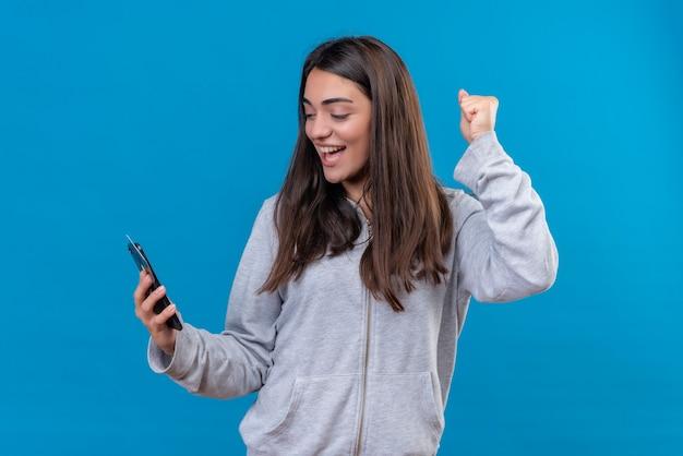 灰色の顔に笑顔で電話を探して、青い背景の上に立っているクレジットカードの電話を保持している灰色の美しい少女
