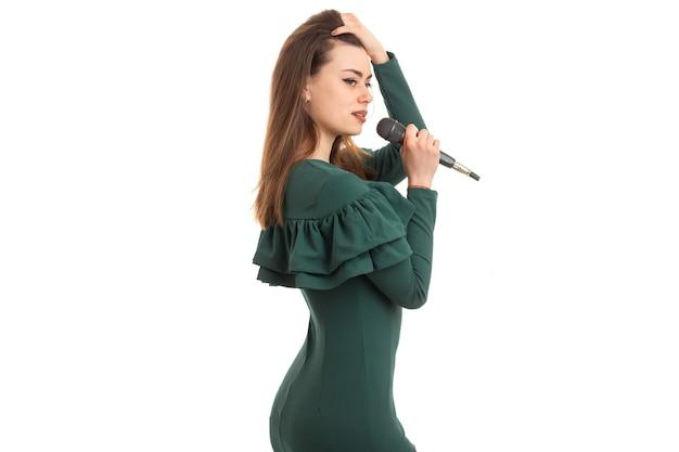 흰색 배경에 고립 된 마이크와 노래방을 노래하는 녹색 드레스에 젊은 아름 다운 소녀