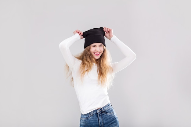 흰색 배경에 스튜디오에서 청바지, 상의, 모자를 쓴 아름다운 소녀