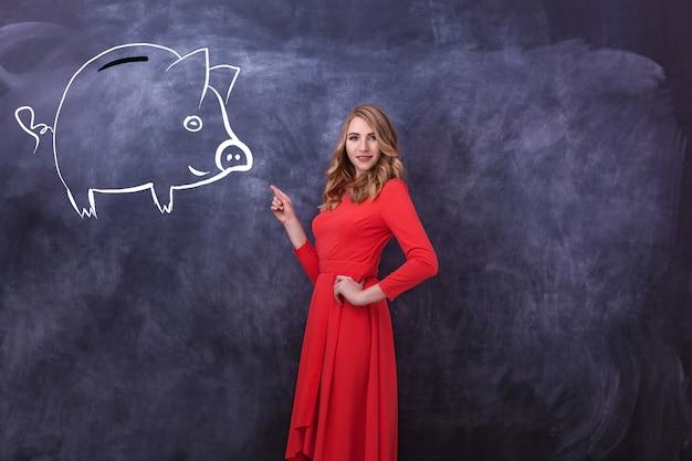 Молодая красивая девушка в красном платье показывает руку на рисунке. на черной доске нарисована свинка-копилка и девочка показывает руку. различные человеческие эмоции, язык тела.