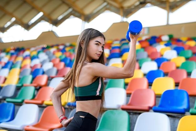夏に市のスタジアムでダンベルを使って運動するスポーツウェアの若い美しい少女。スポーツコンセプト