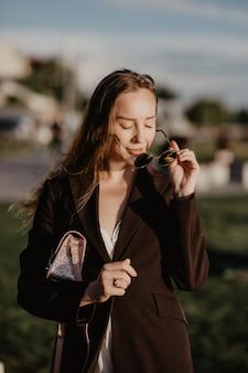 Молодая красивая девушка в стильных солнцезащитных очках и с модной сумкой на закате.