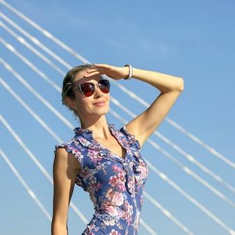 푸른 하늘 배경에서 태양을 바라보는 선글라스를 쓴 아름다운 소녀