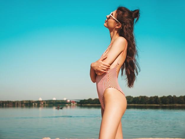 Молодая красивая девушка в солнечных очках позирует на берегу моря, обнимая себя
