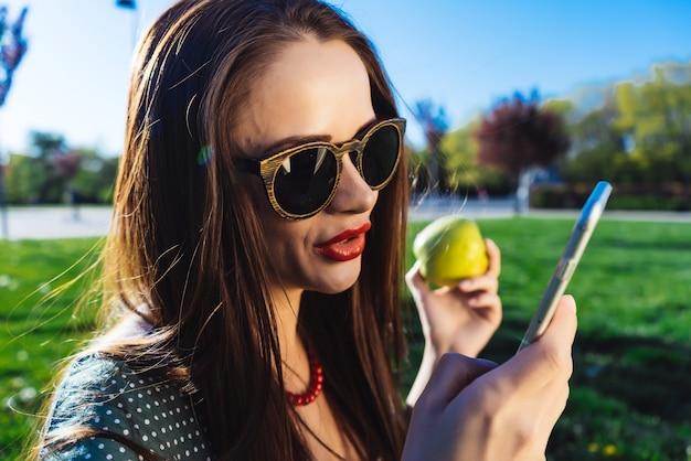 サングラスをかけた若い美しい少女は、明るい緑の芝生と芝生の上に座って、電話で誰かに対応します