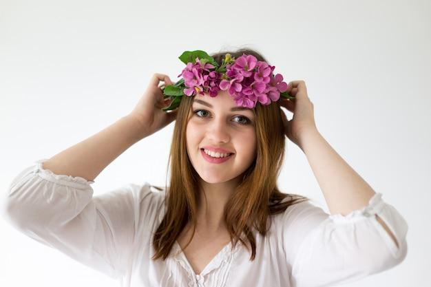 머리에 꽃을 가진 분야에서 젊은 아름 다운 소녀