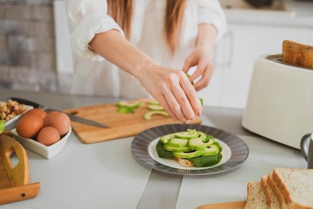 부엌에서 젊은 아름 다운 소녀 건강 식품을 준비 여성의 손을 닫습니다
