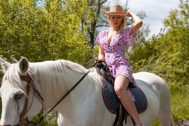 リンク花柄のドレスと自然に白い馬の近くの帽子の美しい少女。ファッションモデルの女の子と馬との屋外写真。