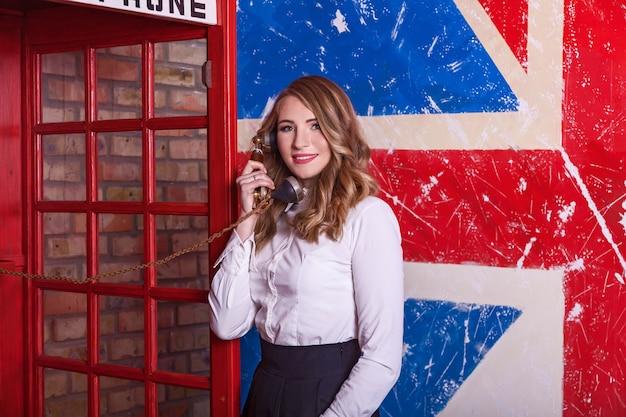 스튜디오에서 흰색 블라우스와 검은색 치마를 입은 아름다운 소녀가 영국 국기 배경의 사진 카메라 앞에서 포즈를 취하고 있습니다. 소녀는 전화로 이야기하고 있습니다. 다른 인간의 감정, 신체 언어.