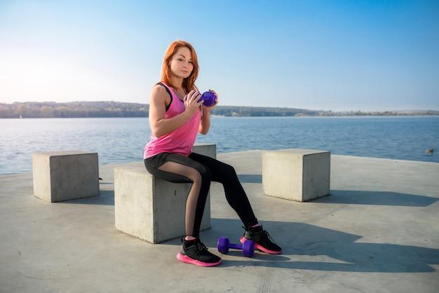 若い美しい少女は湖でダンベルを使って朝の体操に従事しています