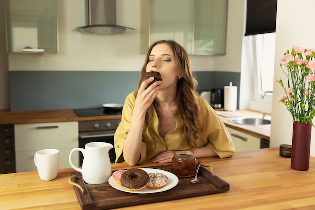 Young beautiful girl is having breakfast at home in the kitchen. she drinks her morning coffee and eats a chocolate muffin.