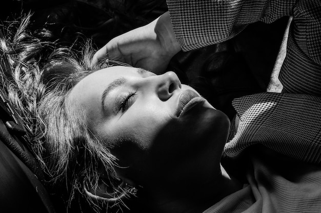 A young, beautiful girl is lying in the back seat of a car. large portrait of a girl. black and white photo.