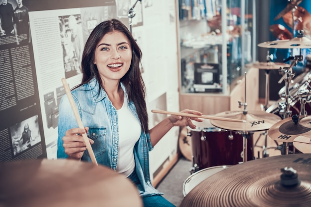 Young beautiful girl is playing on drum kit in music store.