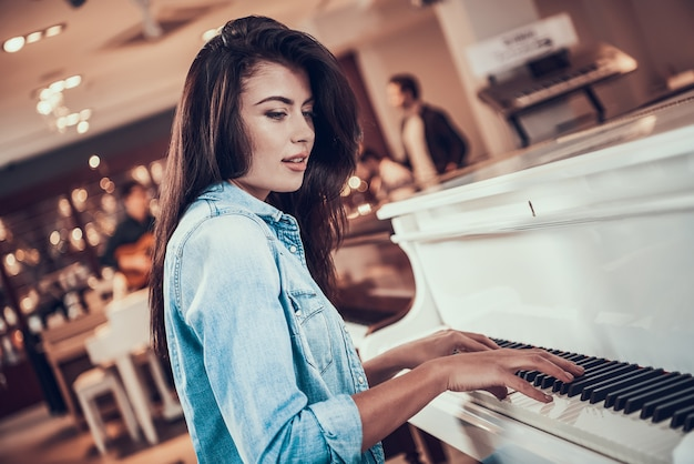Young beautiful girl is playing piano in music store