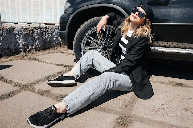 A young, beautiful girl is sitting on the asphalt near her black car in a black jacket, cap and glasses.