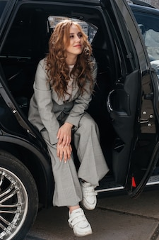 A young, beautiful girl is sitting in the back seat of a car. a stylish girl in a suit gets out of the car.