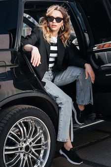A young, beautiful girl is sitting in the back seat of a car. a stylish girl in a suit and glasses gets out of the car.