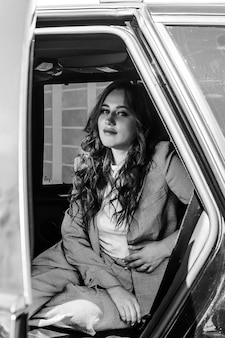 A young, beautiful girl is sitting in a car. stylish girl in a suit large portrait, in the black interior of the car. black and white photo.