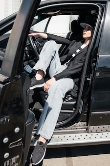 A young, beautiful girl is sitting in the driver's seat. a stylish girl in a suit and glasses opens the car doors