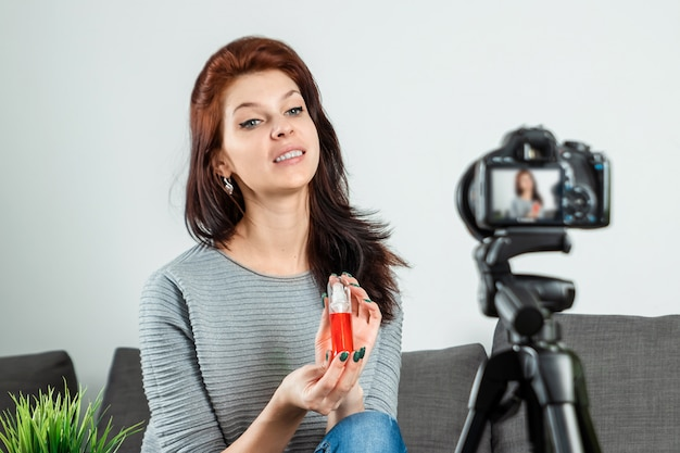 A young beautiful girl is sitting in front of a dslr and recording a vlog, close-up