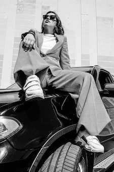 A young, beautiful girl is sitting on the hood of a car. a stylish girl in a suit and glasses on a black car. black and white photo.