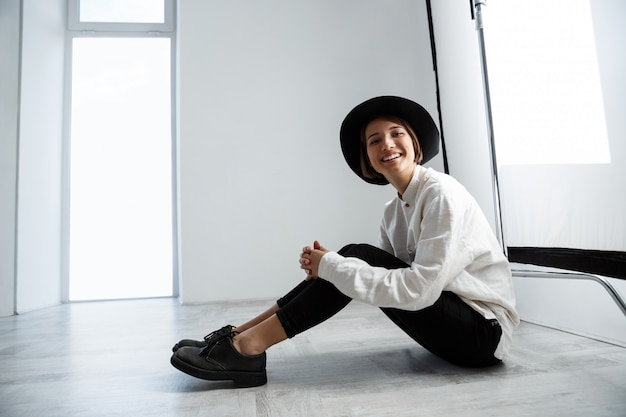 Young beautiful girl laughing sitting on floor over white wall.