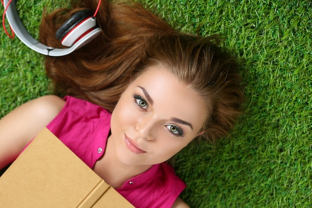 Young beautiful girl laying on the grass in park holding a book. summertime, leisure and education concept top view