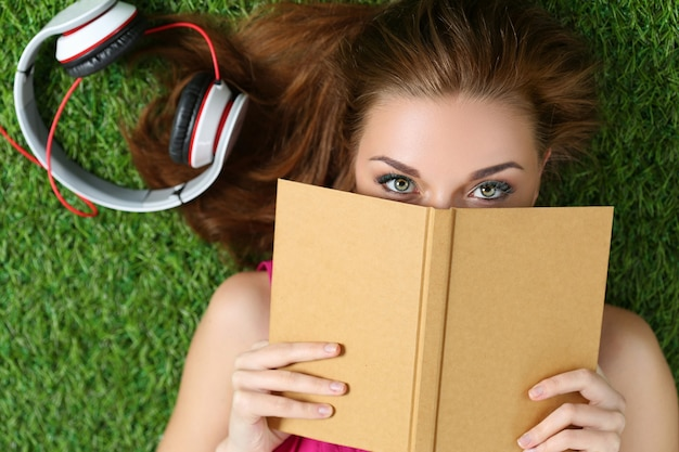 Young beautiful girl laying on the grass in park holding a book. summertime, leisure and education concept. top view