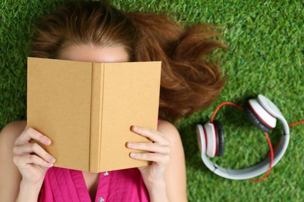 Молодая красивая девушка, лежа на траве в парке, держа книгу. концепция летнего времени, досуга и образования. вид сверху