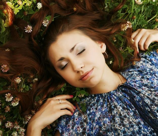 若い美しい少女は草の上に横たわる