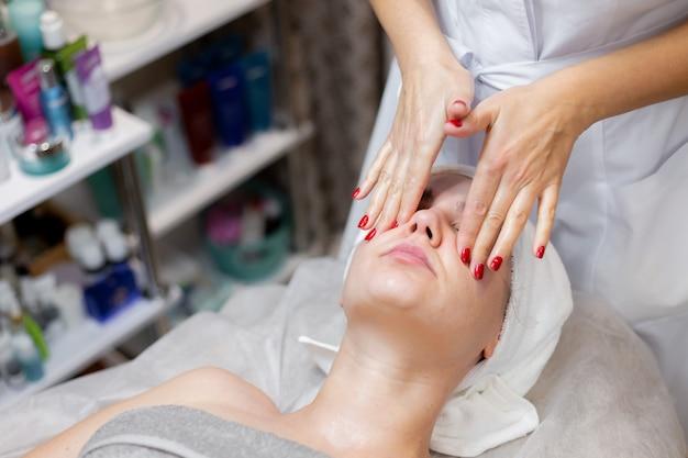 Una giovane bella ragazza si trova sul tavolo dell'estetista e riceve le procedure, un leggero massaggio al viso con olio.