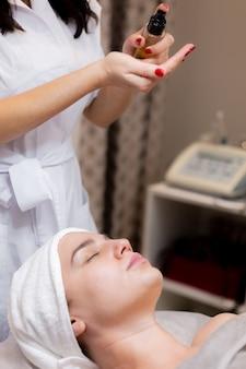 Una giovane bella ragazza si trova sul tavolo dell'estetista e riceve procedure, un leggero massaggio al viso.