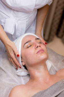 A young beautiful girl lies on the beautician's table and receives procedures, a light facial massage.