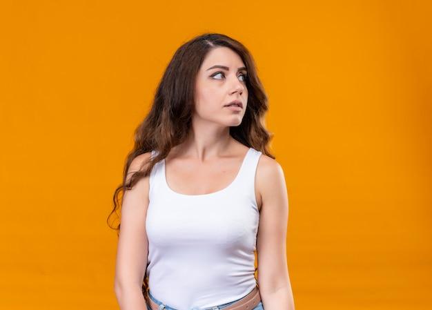Giovane bella ragazza che esamina il lato destro sulla parete arancione isolata con lo spazio della copia