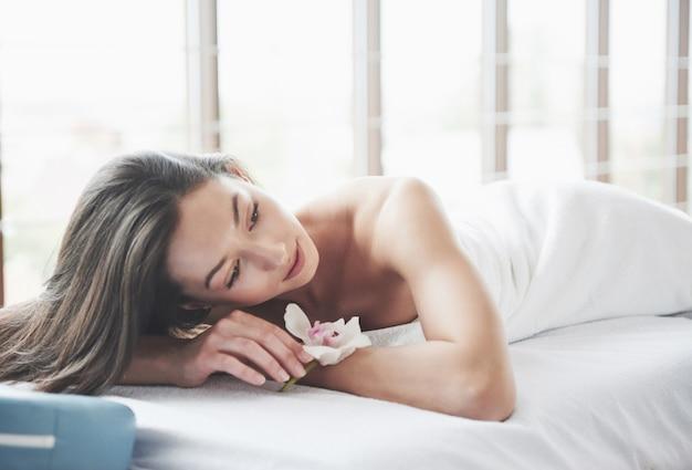Молодая красивая девушка, лежа на массажном столе.