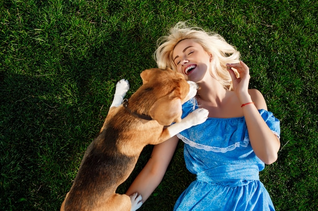 Young beautiful girl lying with beagle dog on grass in park.