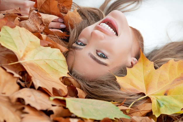 Young beautiful girl lying on yellow leaves in the autumn park.
