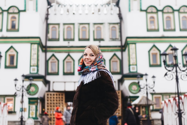 A young beautiful girl in a mink coat walking around in moscow