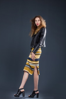 Young beautiful girl model in dress and leather jacket in studio on dark background