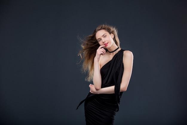 어두운 배경에 스튜디오에서 검은 드레스에 젊은 아름 다운 여자 모델