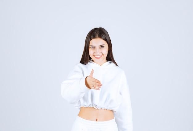 支援と受け入れを与える手のひらの手を提供する若い美しい少女モデル。