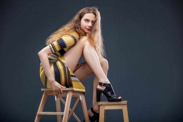 어두운 배경의 스튜디오에서 드레스를 입고 의자에 앉아 있는 아름다운 소녀 모델
