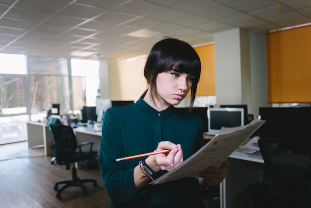 Young beautiful girl office worker looking at business papers and writes something on a background of a modern office.