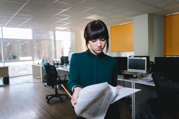 Young beautiful girl office worker with a serious expression reviewing business documents.