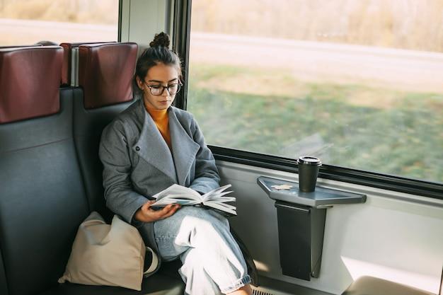 기차에서 여행하는 동안 책을 읽고 기차에 젊은 아름 다운 소녀.