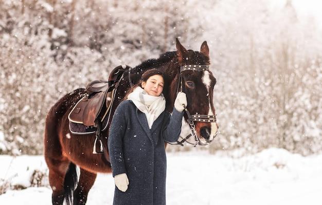 森の中で冬に馬と散歩の若い美しい女の子