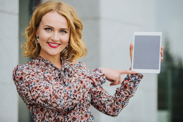 Молодая красивая девушка на улице с планшетом